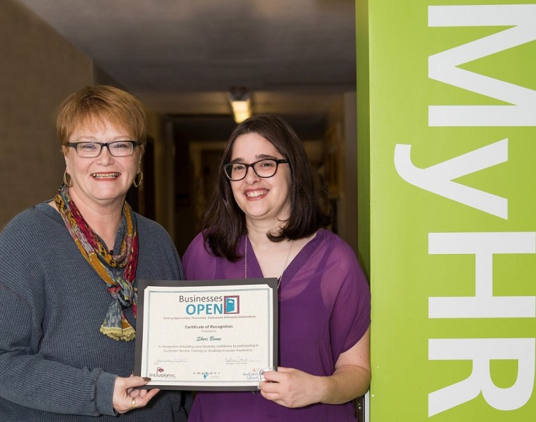 Kathy Hawkins, manager, InclusionNL presents Sheri Boone, MyHR shared services consultant, with certificate for completing Building Disability Confidence training.