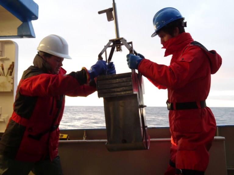 Michelle Kamula, a scientist from the University of Manitoba, and Benjamin Misiuk handling a box core seabed sample aboard the RV Nuliajuk.