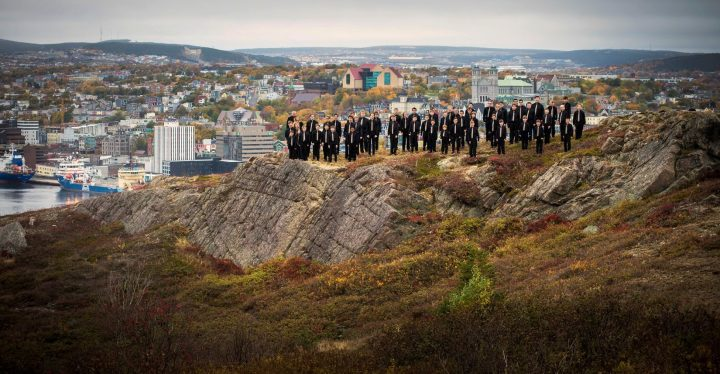 Boys dressed in black suits standing on rock overlooking St. Johns harbour