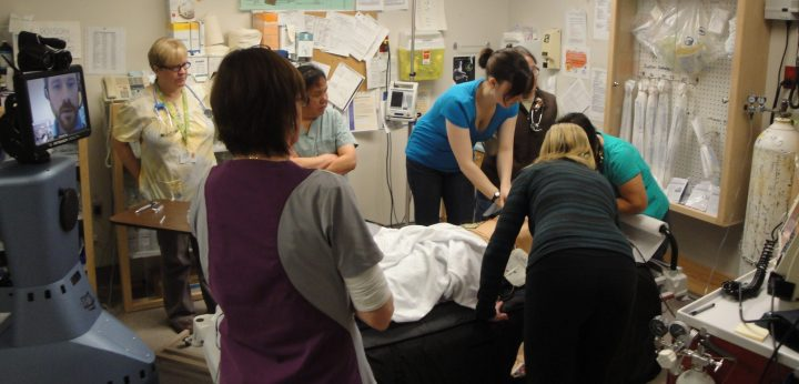 A group stands around a mannequin on a hospital bed, resuscitating a mannequin while a teacher can be seen on a screen
