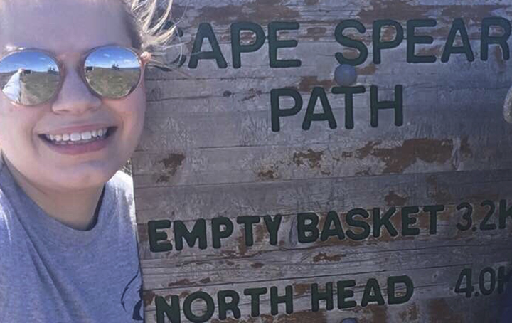 Nicole Noseworthy poses by a sign for Cape Spear Path on the East Coast Trail.