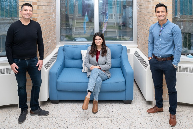 Dr. Bill Walters and Adrian Castro stand on either side of a couch while Ashmita Lamichhane sits on a blue couch.