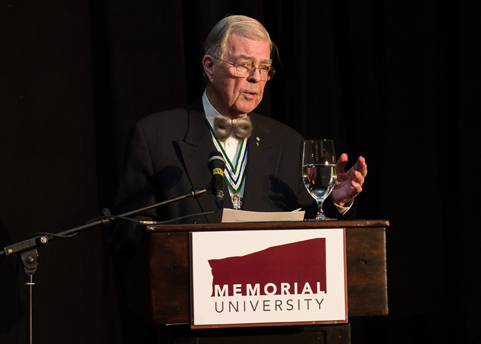 John Crosbie stands at a podium and addresses an audience.