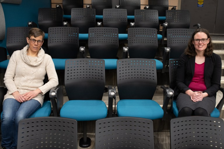 Two women sit six feet apart in a lecture theatre