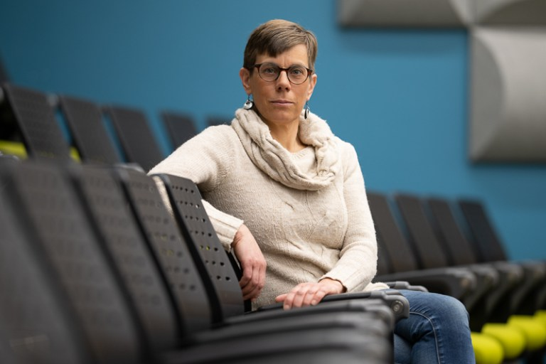 A woman with short grey hair in a cream sweater sits in a lecture theatre
