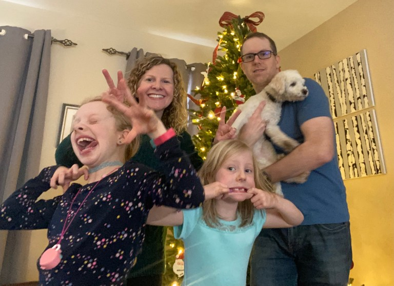 A family of four, plus a white dog, pose for the camera with silly faces in front of a Christmas tree.