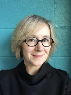 A woman with blonde hair and dark glasses smiles at the camera in front of a blue wall
