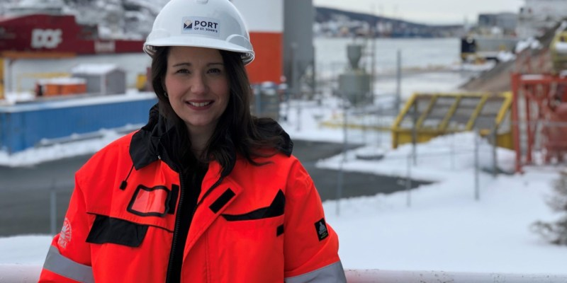 A woman in a white hard hat and orange coat stands in front of a marine industrial area.