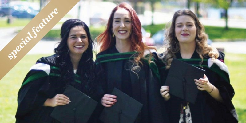 """Three women in graduation gowns hold their mortarboards outdoors. A gold sash with """"special feature"""" is in the upper left hand corner."""