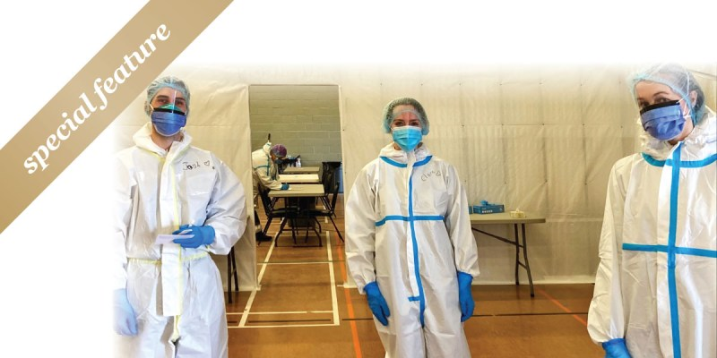"""Three nursing students in PPE gear at a COVID-19 swabbing clinic in a gymnasium. A gold sash with """"special feature"""" is in the upper left hand corner."""