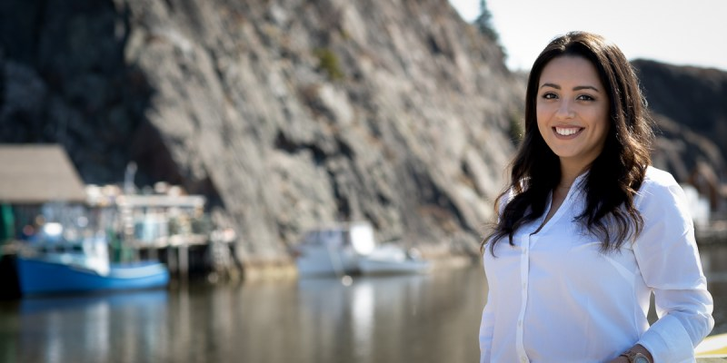 A woman with brown hair and wearing jeans and a white shirt stands in front of Quidi Vidi gut.