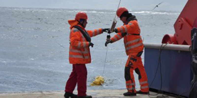Two people in safety gear pull up a rope from the ocean