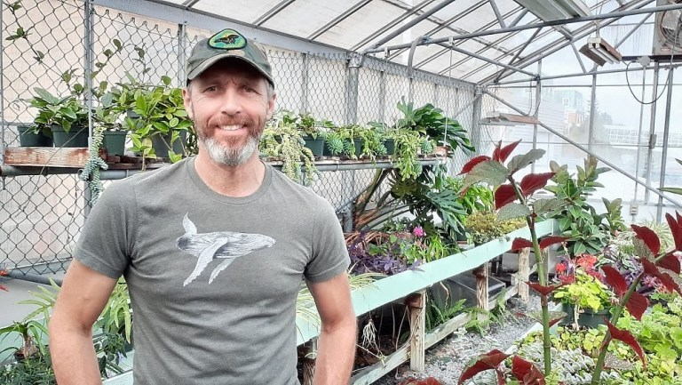 A man with a beard and grey hat and t-shirt stands in front of flowers in a greenhouse.