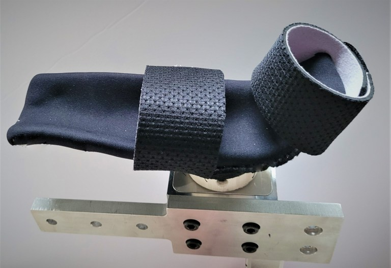 A black cushioned arm rest with two black straps attached to a metal component.