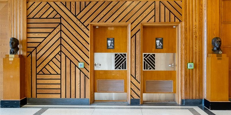 The doors to two gender-inclusive washrooms in the Arts building on the St. John's campus. They have signs on the doors and are surrounded by a black zigzag pattern on warm yellow wood.