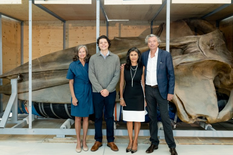 Lisa, Michael, Sandra and Mark Dobbin stand in front of a blue whale skull in a wooden crate.