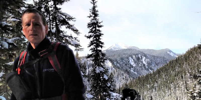 Dr. Greg Naterer is pictured in a black jacket and backpack with snow-covered trees and mountains behind him.