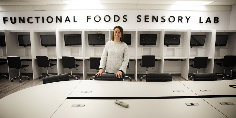 Natalia Prieto Vidal stands in front of a white wall of computer cubicles behind and a white desk in front in the Functional Foods Lab at Grenfell Campus.