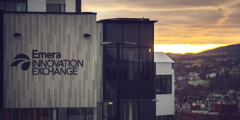 The Emera Innovation Exchange on Signal Hill Campus, a grey, white and black building, is seen at dusk with downtown St. John's visible in the background with a setting sun.