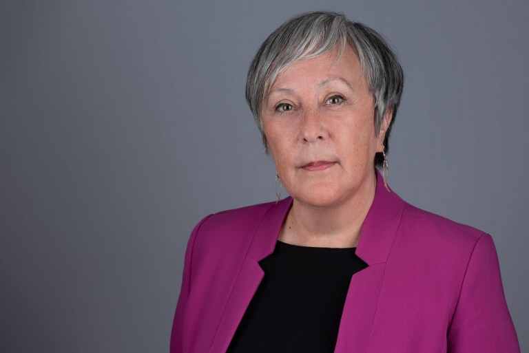 Violet Ford, wearing a black shirt and pink-coloured jacket, poses for a photo.