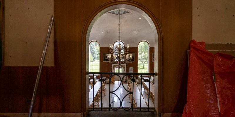 An arched, open balcony with a railing that looks into a large double height dining room. A large chandelier hangs in the middle of the image.
