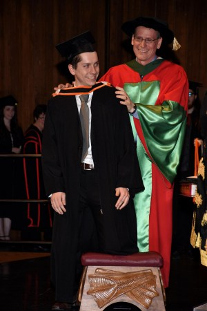 Jordan Naterer receives his orange engineering hood from his father Dr. Greg Naterer on stage at convocation. Dr. Naterer wears the red and green gown as the dean of engineering.