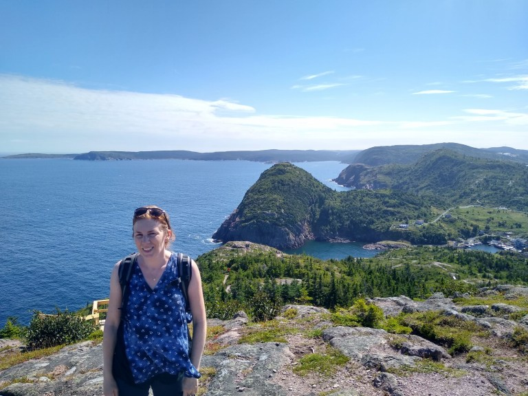 Dr. Kathryn Hargan wears a blue-coloured short sleeved shirt and backpack. The ocean, green trees and rugged coastline are in the background.