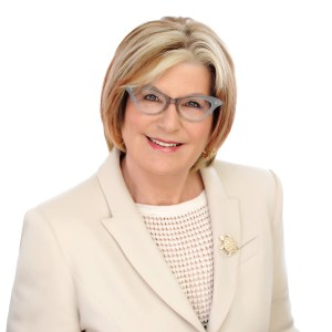 Louise Bradley wears grey glasses and a cream suit with a gold brooch.