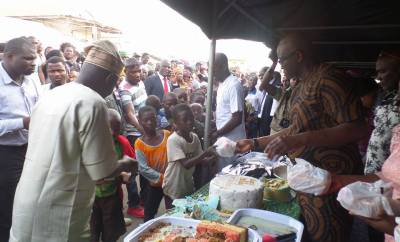 Governor Fayose treats little children to pieces of cake at his 57th birthday street party