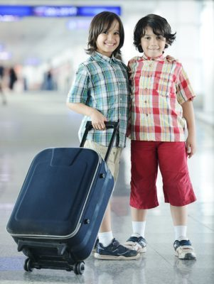 Travel Insurance in English for Expats. GB Insurance Services, Madrid, Spain. Young boys with suitcase.