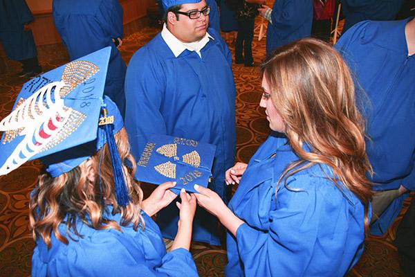 Galveston College graduates admire decorated cap at ceremony