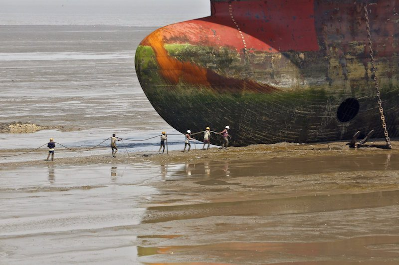 Workers carry a rope line to fasten a decommissioned ship at the Alang shipyard in Gujarat, India, in this March 27, 2015 file photo. REUTERS/Amit Dave/Files