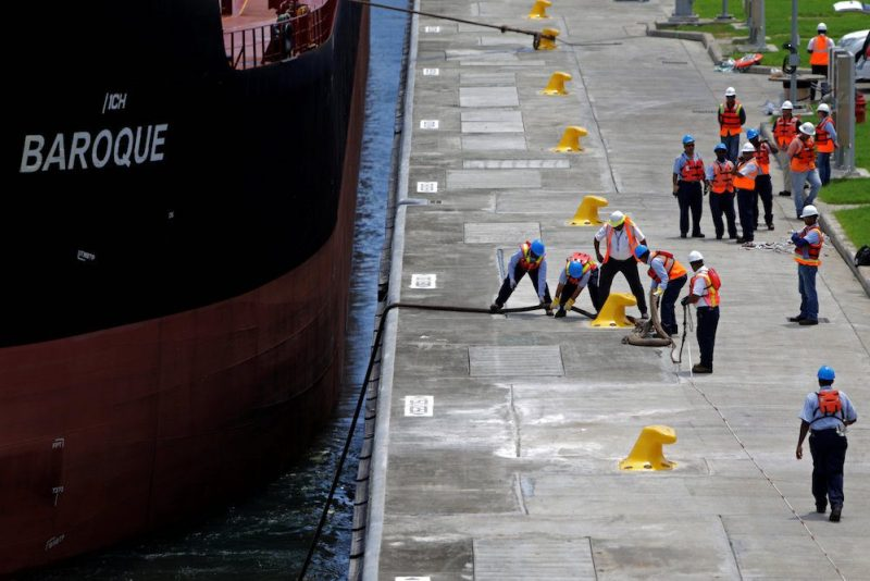 Workers pull the rope during the first trial run of a Post-Panamax cargo ship in the new sets of locks on the Atlantic side of the Panama Canal, in Panama City, Panama June 9, 2016. REUTERS/Carlos Jasso