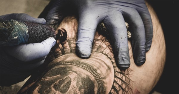 A close up of a person getting a tattoo of a skull on their arm