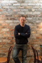 Temple Garner, the chef and owner of San Lorenzo's in front of a brick wall