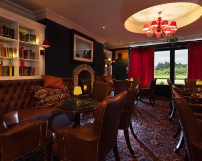 An interior shot of the lodge at ashford castle where if you book a wedding, you could win a luxury cruise to the value of e10000 with chairs and couches in a rich looking room
