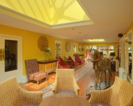 An interior shot of the lodge at ashford castle where if you book a wedding, you could win a luxury cruise to the value of e10000 with chairs and couches in a brightly lit yellow tinged room