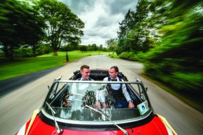 Andrew and thomas driving in a red convertible from Andrew and Thomas' Real Weddings article