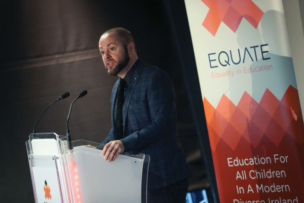 Michael Barron speaking in front of an equate banner about Irish schools and secular reform