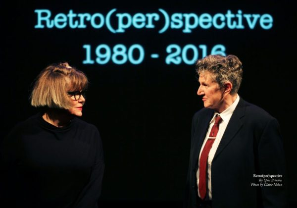 Two people with the word Retro(per)spective written behind them on a black wall as part of Live Collision 2017