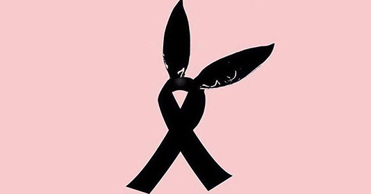 A pair of bunny ears from Ariana Grande's single 'Dangerous woman' atop a black ribbon on a pink background to represent those killed and injured at the Ariana Grande concert in Manchester Arena