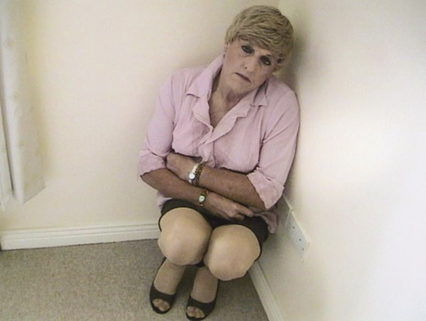 Christine Beynon from the art exhibition in Becoming Christine in a pink blouse sitting in a corner with her arms crossed