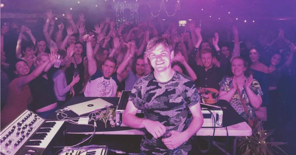 Dj Daithí stands in front of a crowd in a club