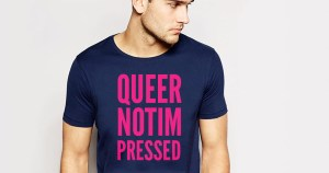 A person wearing a t-shirt that says Queer Not Impressed on it in pink after an employee of the t-shirt company wrote those words in an email which Gay Switchboard Director Adam Shanley received