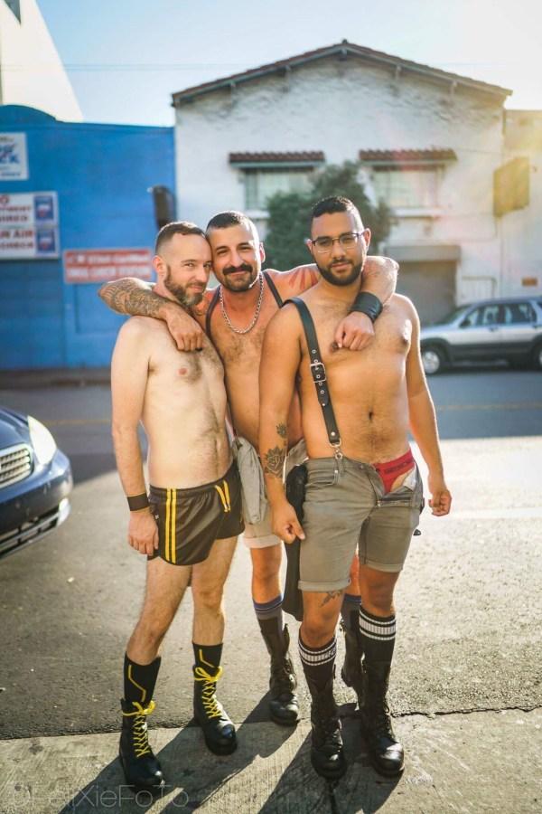 Three shirtless men in shorts hugging at Folsom Street Fair