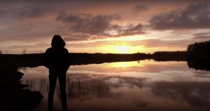 Elaine Mai standing in a hoodie in front of a lake at sunrise