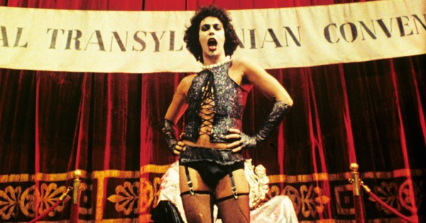 Dr Frank-N-Furter standing in front of a banner while singing. He is the top pick as most Iconic LGBT+ character in horror movies