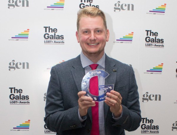 Broden Giambrone, who won person of the year at The GALAS 2017, holding his award in front of a branded background