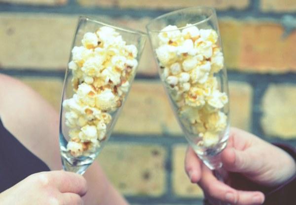 Cornude popcorn in champagne glasses against a brick wall background