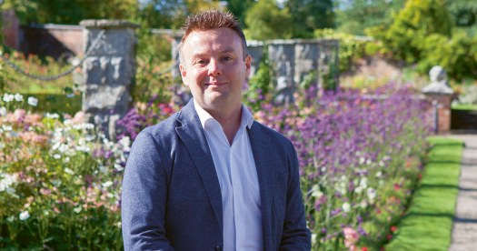 Daragh Doyle, the wedding planner from Rainbow Weddings, wearing a blue suit jacket in front of gorgeous purple flowers and a green lawn